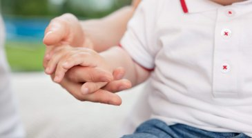 Close-up of mother holding child's hand